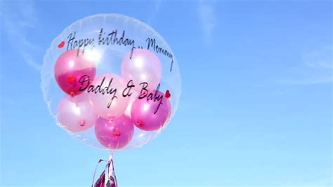 A happy birthday balloon with words quot happy birthday mommy from daddy amp baby quot floating in blue