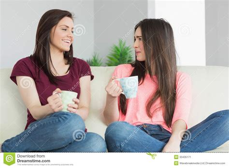 two girls having on couch two girls sitting on a sofa looking each other and