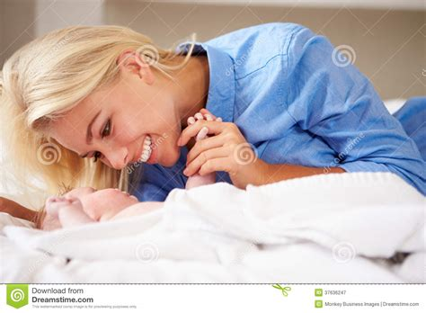 lie in bed mother playing with baby girl as they lie in bed together royalty free stock