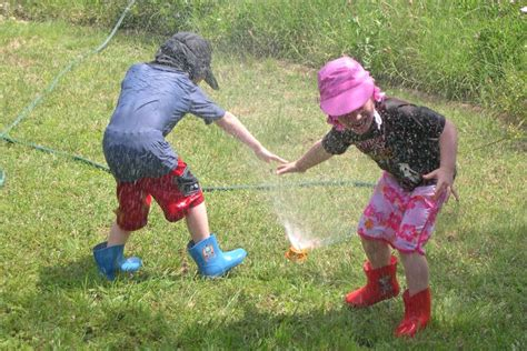 kids playing in backyard photo of kids playing under sprinkler in backyard at