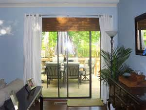 Sliding doors treated like window with white curtains on either side