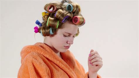 men with red fingernails and curlers in hair face of teenage girl of 13 years old wearing bathrobe in