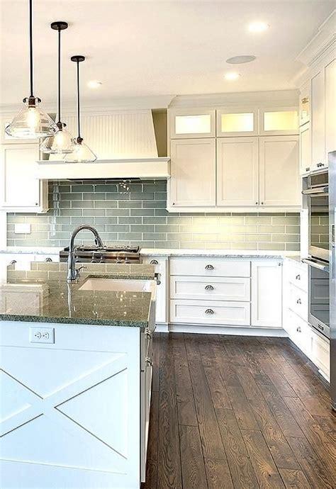 granite topped kitchen island three glass pendants hang a white kitchen island