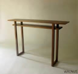 modern narrow console table made from wood metal and glass
