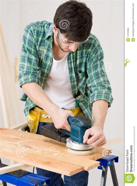 home improvement handyman sanding wooden floor stock