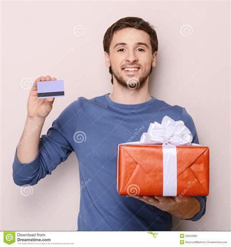 portrait of young man holding gift box and a credit card handso royalty free stock - Gift Cards For Young Men