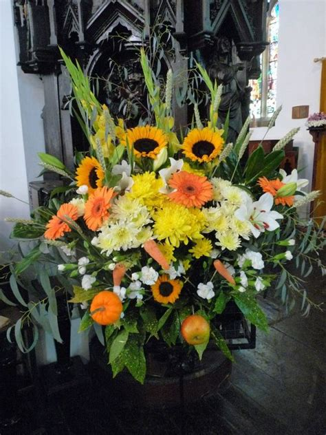 harvest festival flower arrangement in church with sunflowers mini pumpkins carrots and apples