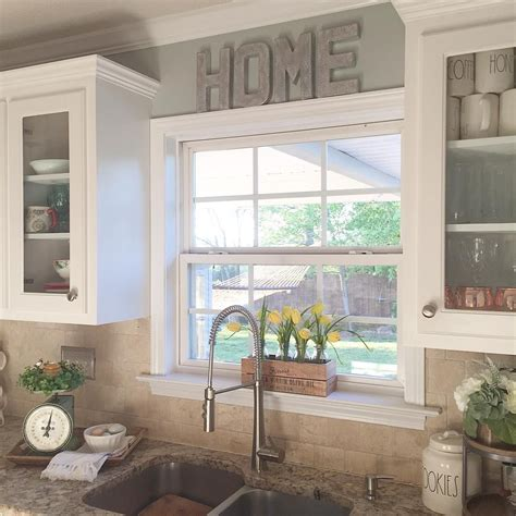 kitchen window decorating ideas i like the raised window and the glass cabinets around it