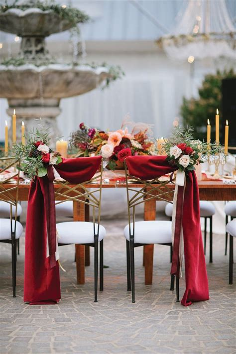and groom chair decor with scarlet fabric draping and autumn florals fall wedding florals