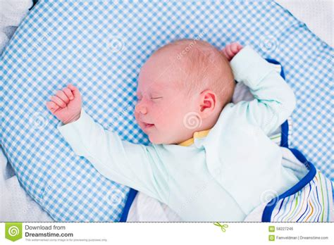 swaddled baby in white bed stock photo image