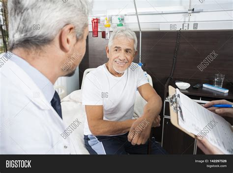 Rehab Doctors 2 by Senior Patient Looking At Doctor In Rehab Center Stock