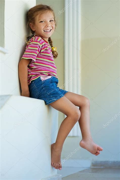 tiny petite little girl in shorts sitting stock photo