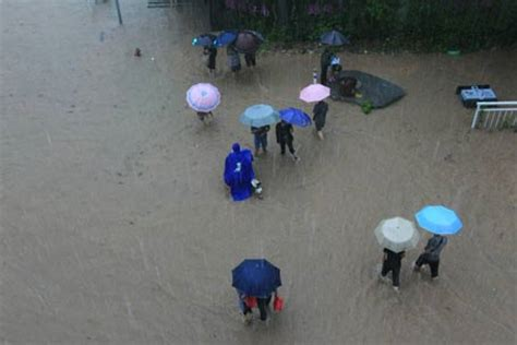 emirates global aluminium cuts 250 jobs amid global oversupply pedestrians wading through a heavily flooded street in