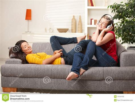 girls having on a couch teen girls listening to music on couch stock photography