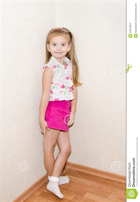 tiny small cute little girl standing near the wall royalty free stock