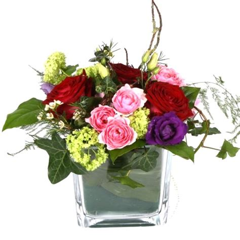 reds purples and pinks flower arrangement in clear glass