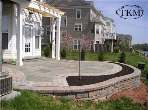 3d House Design raised flagstone patio with segmental wall and paver trim