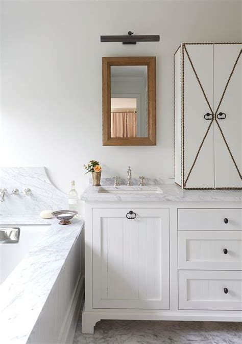 White Beadboard Bathroom Vanity Cottage Bathroom Features A White Vanity Accented With White Beadboard Doors Adorned With