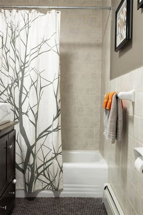 lovely guest bathroom design with warm gray walls displaying framed butterfly and gray tiled