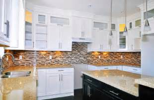 White cabinetry all around patterned micro tile backsplash in earth