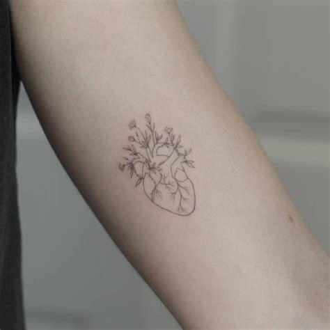 small heart tattoos on arm single needle flower on the left inner arm