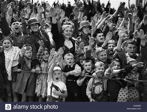 biography of hitler for students german children and soldiers give the nazi salute during