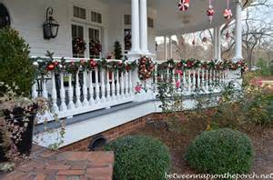 Porch rail on victorian home decorated for christmas