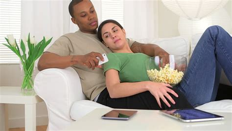 family watching tv with popcorn in living room stock photo young couple watching tv on the sofa in the living room