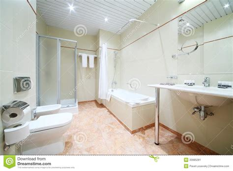 image of a bathroom light and empty bathroom with white bath toilet stock