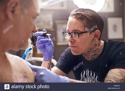 focused tattoo holding gun to stock photos holding gun to