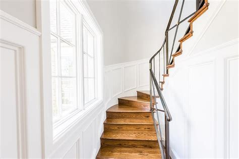 narrow winding staircase with paneled walls transitional