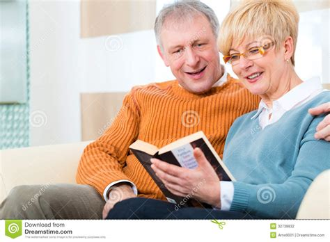seniors and elders embrace books seniors at home reading a book together stock photography