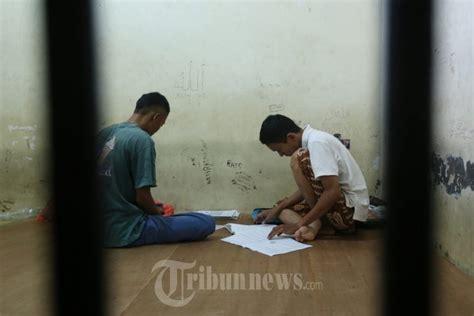 Bisnis Di Balik Jeruji dua murid mengerjakan un dibalik jeruji mapolsek foto 4