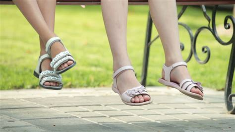 wearing sandals of two sitting on bench wearing sandals