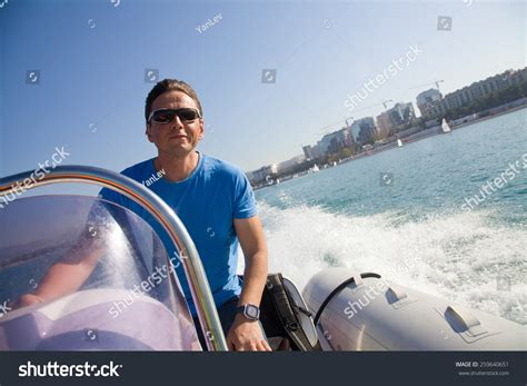 boat driving man man driving an inflatable motor boat at a speed rushes to