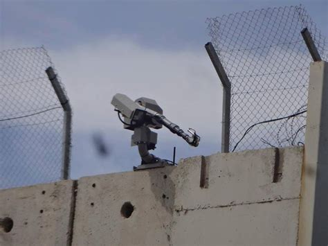 remote machine gun installed on top of wall near