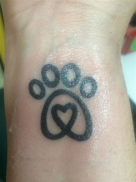 dog with tattoo paw in memory of pluto ink