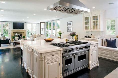 Kitchen island viking range white kitchen dark wood floors window seat