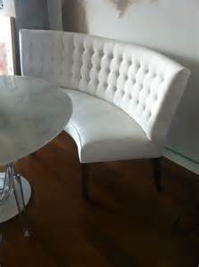 White curved banquette seating ideas with tufted bench and round table