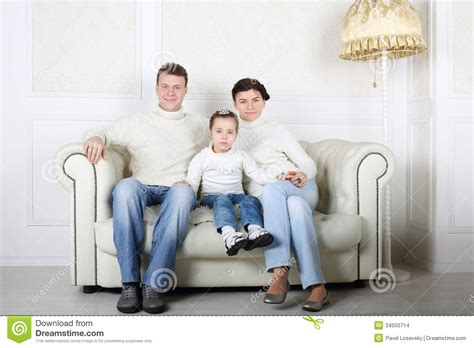 white couch with kids happy family in white sweaters and jeans sit on white sofa