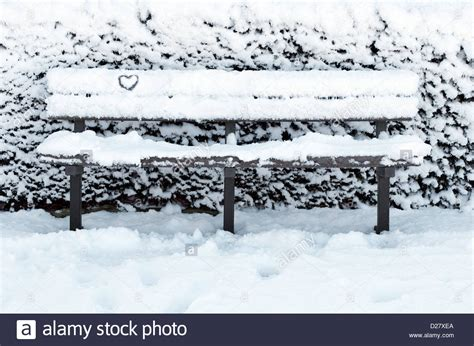 bench in snow snow covered park bench in winter norfolk england stock