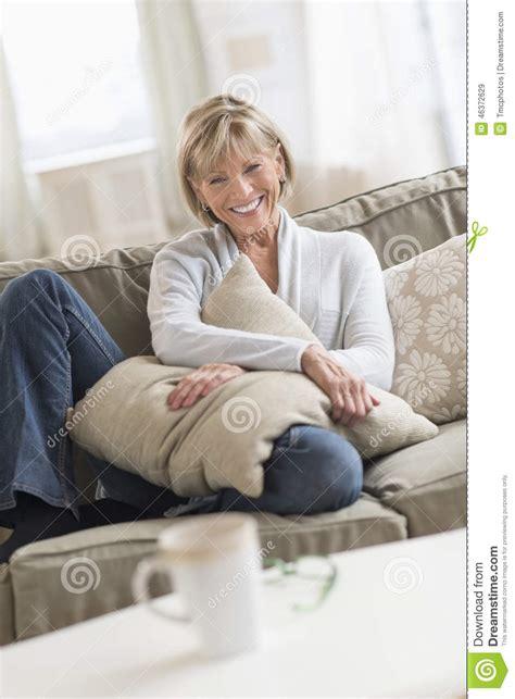 mature sofa happy mature woman with cushion sitting on sofa stock