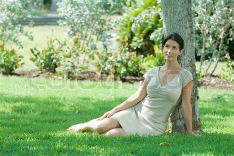 beautiful woman by the tree looking up stock photo image woman sitting on the ground under tree smiling looking
