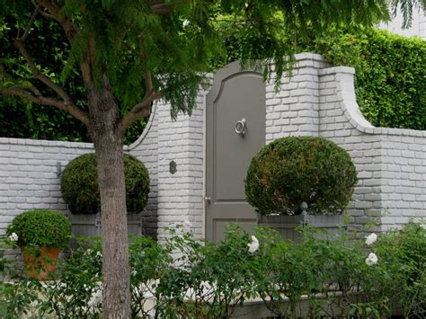 painted garden gate in painted brick wall boxwood