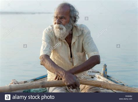 old man rowing a boat on the ganges river sunrise - Old Man On Boat