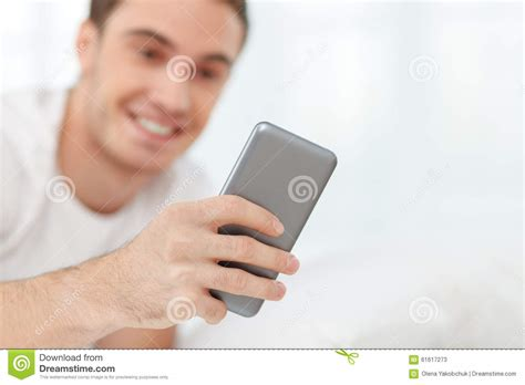 man using cell phone in bed stock images image 33817024 attractive guy is using telephone in bedroom stock photo