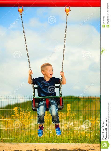 kid active swing little blonde boy child having fun on a swing outdoor