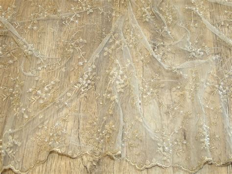 above delicate lace hand beaded with hundreds of glass beads soft delicate beaded scalloped edge couture bridal lace fabric