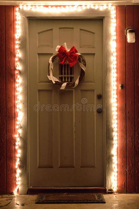 old fashioned christmas lights white christmas lights and wreath on front door at night stock