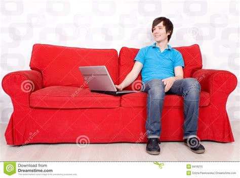 sitting on a sofa man sitting on couch with laptop royalty free stock photo